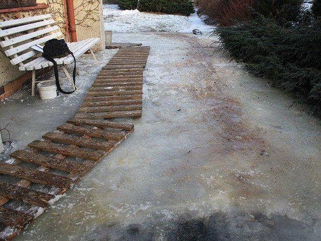 PŘÍSTUPOVÁ CESTA k domu se kompletně změnila v ledovku s několik centimetrů silnou vrstvou ledu. Obyvatelé museli na pomoc přivolat plánské dobrovolné hasiče.