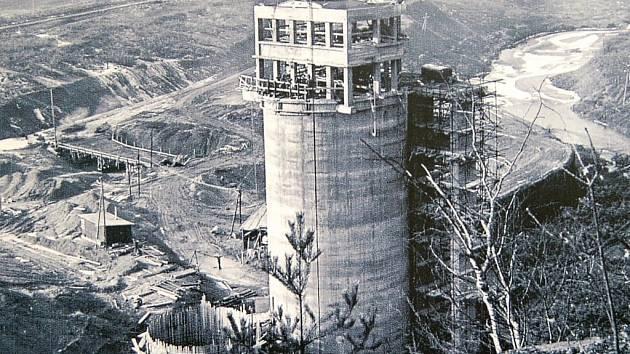 STAVBA PŘEHRADNÍ HRÁZE na Hracholuské přehradě. Rok 1962. Věž budoucí elektrárny již stojí celá.