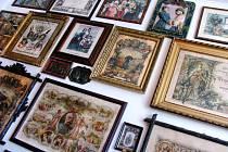 STĚNY PLNÉ OBRAZŮ. Vitríny s dobovými předměty, hrnky, skleničkami ale i různými kukátky a bysty různých velikostí. Police od podlahy ke stropu zaplněné knihami, pohlednicemi a fotografiemi a stěny, na kterých jsou obrazy, diplomy či vyznamenání.
