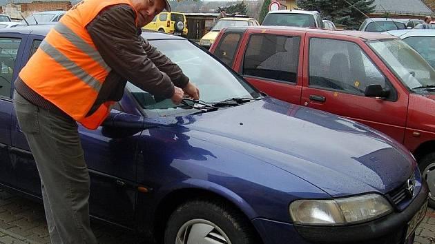 Hlídač placeného parkoviště ve Stříbře, Zdeněk Fikejzl, dává neplatičům lístky s upozorněním za stěrač auta.