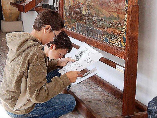 ŘEŠENÍ TESTU. Děti z Tachova i německého Weidenu strávili středeční dopoledne v tachovském muzeu. Součástí bylo také samostatné vyplňování testu, odpovědi si žáci sami vyhledali v expozici.