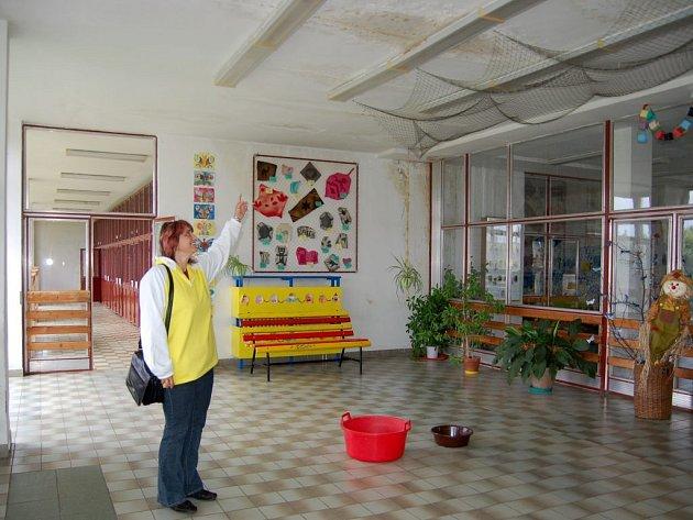 Místostarostka obce Staré Sedliště Jitka Valíčková ukazuje následky poškozené střechy v místní škole.