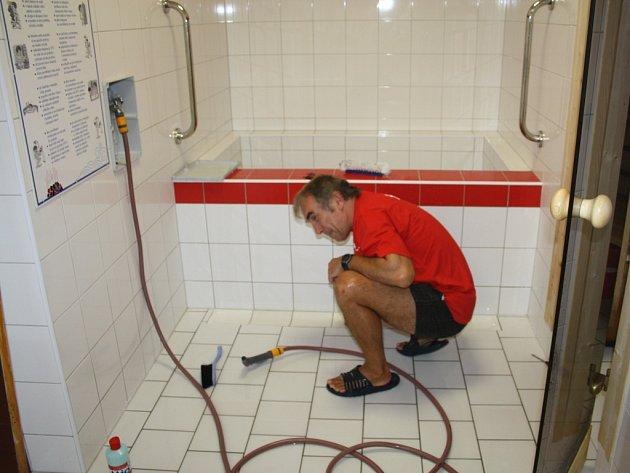 PRAVIDELNOU ODSTÁVKOU prochází v těchto dnech tachovský bazén. Rekonstrukce sprch je dokončena, nadále se pracuje na instalaci nových vířivek. Na snímku při úklidu v nových sprch a sauny plavčík Jaroslav Šebek.