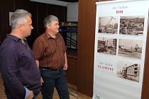 Petr Nyč a Pavel Šatra ze Stavebního bytového družstva Tachov před jedním z osmnácti fotopanelů přinášejících pohled na historii domů.
