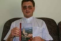 Farář Václav Vojtíšek ukazuje pamětní brožuru o historii tachovského kostela Nanebevzetí Panny Marie.