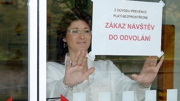 VRCHNÍ SESTRA Nemocnice následné péče na Svaté Anně Miroslava Kordíková lepí na vstupní dveře oznámení o zákazu návštěv v nemocnici.