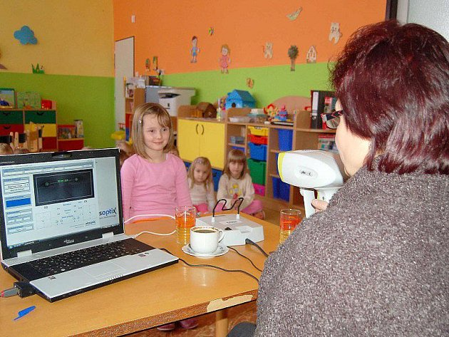 VYŠETŘENÍ ZRAKU. Zdravotní sestra vyšetřuje zrak takzvaným videoretinoskopem, který umí na místě zjistit oční vady u vyšetřovaných osob.
