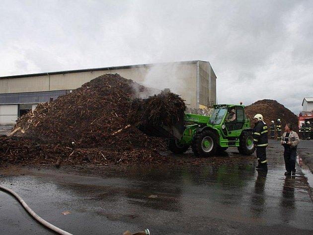 Hořící kůru a dřevěné štěpky musely stroje rozhrnout a hasiči pak oheň postupně dohasili.