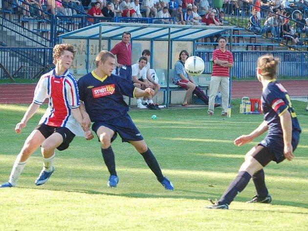 Fotbalisté FK Tachov remizovali na městském stadionu s favorizovanou Jiskrou Domažlice 2:2. Na snímku zastavuje mladíčka v dresu domácího celku Tomáše Habarta (vlevo) dvojice domažlických obránců.