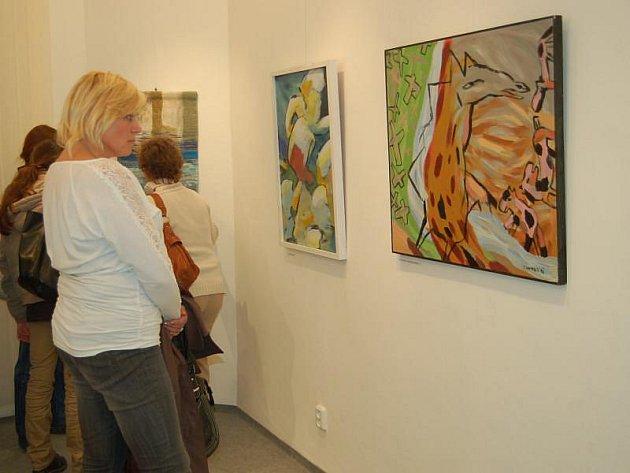 Návštěvníci Městské galerie v Tachově při prohlídceobrazů získaných darem od výtvarníků.