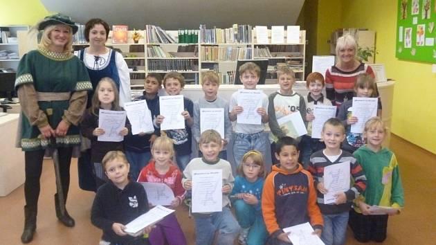 NOVOPEČENÍ ČTENÁŘI. Žáky druhé třídy z Kostelní školy pasoval na čtenáře rytíř Knihomol v podání Hany Herdové (vlevo).