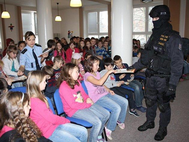 Policisté rozdávají preventivní letáky školákům.