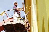 Pracovníci stavební firmy provádí nátěr budovy školy v Kostelní ulici.