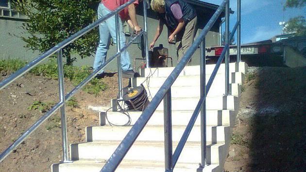 Na snímku zleva vrtá Jaromír Musil dítu na šrouby. Asistuje mu jeho žena Dana Musilová. Obyvatelé sídliště Východ se tak v podobě schodiště dočkali dalšího přístupu k lokalitě, kde jsou autobusové i vlakové nádraží, úřady a obchody.