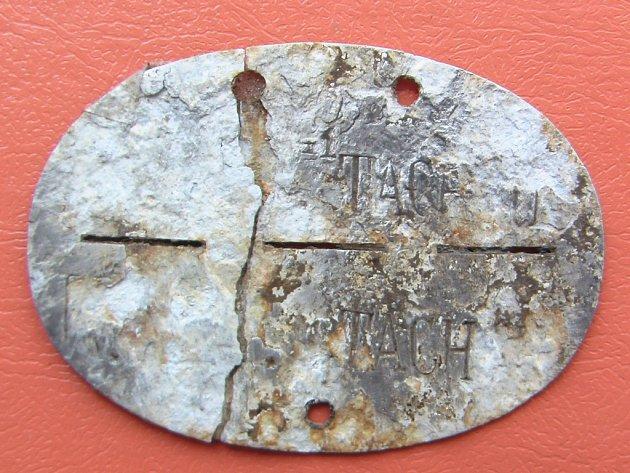 Identifikační vojenská známka s nápisem, který pravděpodobně nese jméno města Tachov.