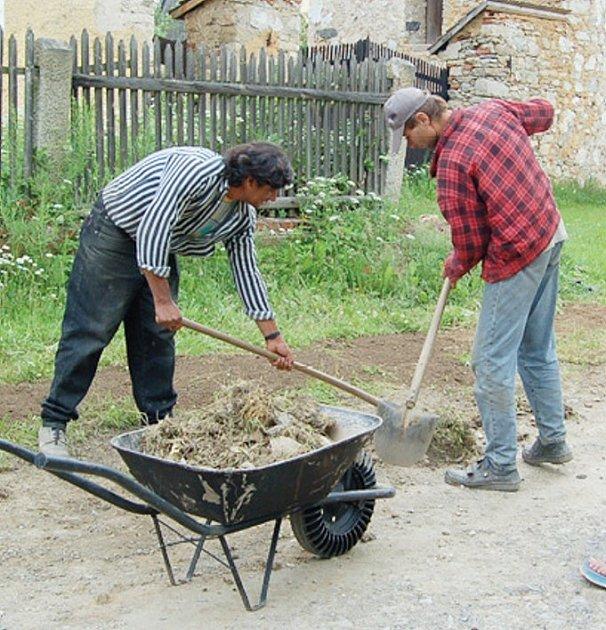 Dělníci upravují povrch kudy vedou roury, kterými povedou dráty.