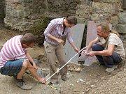 Archeolog ukazuje kosterní pozůstatky nalezené ve Stříbře.