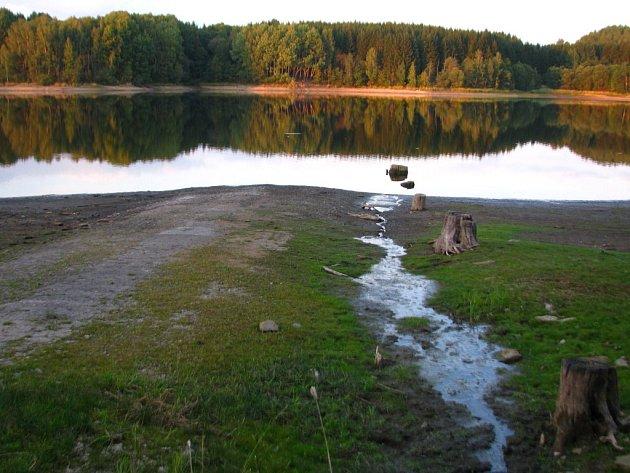 BÝVALÁ SILNICE DO LUČINY pařezy, zbytky cihel a podezdívky budov zaniklé obce Lučina postupně vykukují z vody nádrže. Hladina je v současné době o téměř jeden metr pod optimální úrovní. Dokud nezaprší, bude dále klesat.