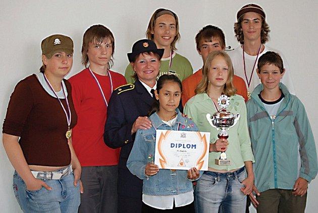 Členové vítězného družstva mladých hasičů ze Studánky se při návštěvě u starostky obce nechali vyfotografovat i s jejich trofejí a vedoucí Evou Jančovou.