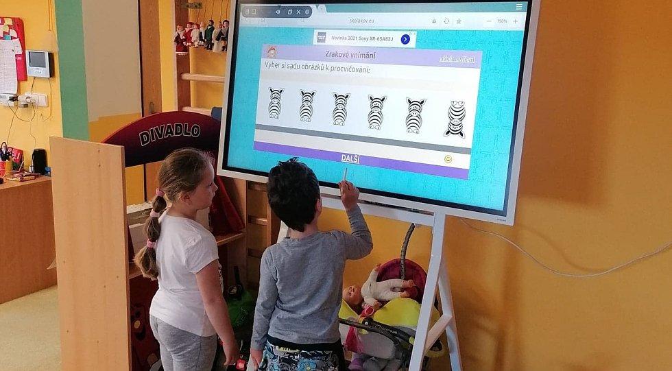 Děti mateřinky ve Studánce se radují z interaktivní tabule.
