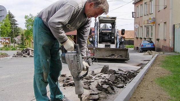 Michal Houdek rozbíjí starý asfalt, aby obubníky pořádně zajistil.