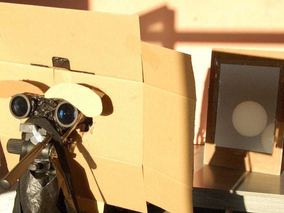 Jednoduché pozorovací zařízení se skládá z triedru na stativu, kartonu a bílého papíru. Vpravo v pozadí je vidět promítnutý sluneční disk.