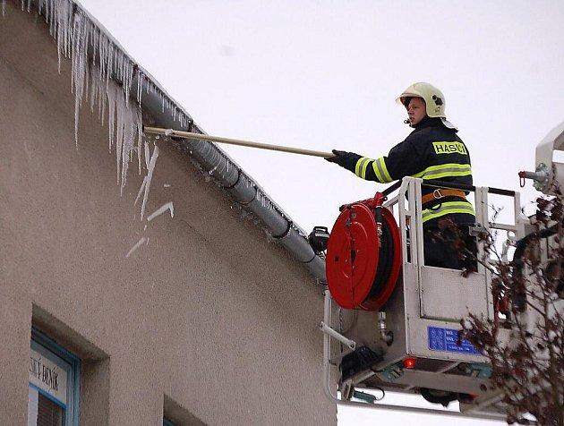JAROMÍR SÍTAŘ z tachovské stanice Hasičského záchranného sboru v plošině shazuje ledové rampouchy z okapu objektu, ve kterém sídlí Tachovksý deník.