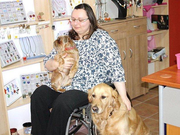 Lenka Lašková je po autonehodě od patnácti let na vozíku. Přesto dokáže žít i pracovat naplno. Pomáhají jí v tom asistenční pes, zlatý retriever Bela a bruselský grifonek Mija.