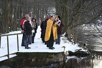 Při pobožnosti na břehu rybníka namočil kněz do vody všechny symboly používané při liturgiích, včetně tohoto svícnu.