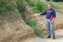 Martin Pohl ukazuje na místo, kde byl dříve vjezd na jeho pole. Nyní tam je navezen několik metrů vysoký val, který tam vznikl v rámci  výstavby nové úvozové cesty.