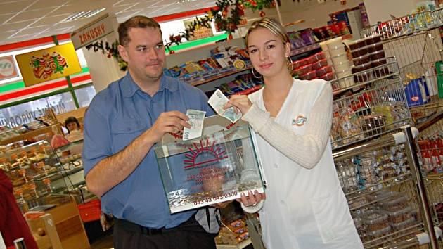 Jaroslav Vacata a pokladní z prodejny potravin v Tachově Taťana Semchuk  drží kasičku Nadace pro transplantaci kostní dřeně.