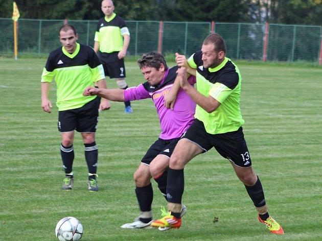 SNÍMEK Z UTKÁNÍ mezi Dynamem Studánka a Sokolem Lom. V souboji o míč domácí Martin Vlček (ve fialovo-černém) s lomským Yuriem Kalynichem.