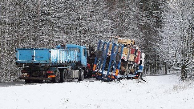 Kamion zůstal naklopený nad příkopem. Na pomoc přijela těžká technika