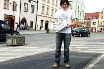 Pracovník tachovského městského kulturního střediska Pavel Voltr drží knihu Tachovsko na starých pohlednicich, kde je na jedné z fotografií ukázáno, jak náměstí vypadalo na počátku 20. století.