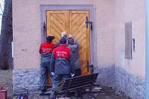 Instalace nových vchodových dveří v kostele Petra a Pavla v Milířích. Kostel čeká ještě řada dalších oprav.