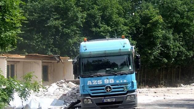NA MÍSTĚ, kde stála ubytovna pro neplatiče, je nyní zástup nákladních vozů a demoličních strojů. Ubytovna padá k zemi a všude je spousta prachu.