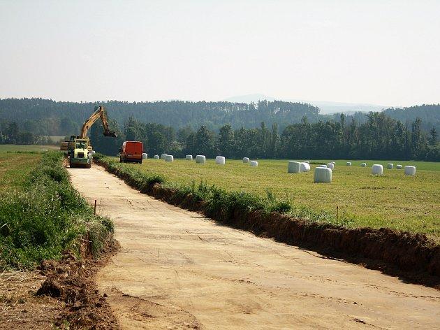 Stavební firma při práci na nové asfaltové polní cestě ve směru od Částkova na Pernolec.