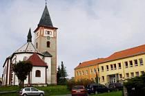 ZATÍMCO FASÁDA školy je zánovní (vpravo), kostel by si podle obyvatel Stráže novou fasádu zasloužil rovněž.