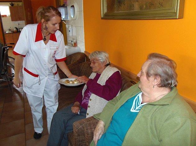 CHARITA SE PŘEDSTAVILA. Lucie Zichová nabízí chuťovky návštěvnici Jindřišce Šrámkové, která přišla za Marií Paškovou (vpravo).