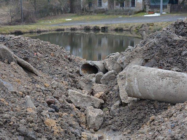 Několik náklaďáků navezlo hlínu na náves obce Štokov. Obyvatelé se bojí, že se plno odpadů, který v hlíně je, skryje pod trávu.