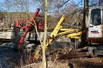 POMOCÍ TĚŽKÉ TECHNIKY odstraňovali pracovníci Povodí Vltavy ledové kry na Úterském potoce.
