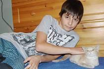 Kocourek Tedy se po zranění, které si podle veterináře nemohl způsobit sám, zotavuje pomalu. Skoro se nemůže hýbat. Na snímku jej hladí třináctiletý Standa Kokrment.