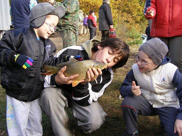 Kapr, kterého vyhráli manželé Kastlovi v tombole na Rybářském plese, dostal pusu od Tomáše Houžvičky, radost měli i Pavlík a Martin Kastlových (zleva).