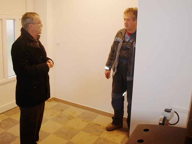 Starosta Kostelce František Trhlík se ptá pracovníků, jak pokračují konečné úpravy uvnitř společenské klubovny. Ti nyní montují novou kuchyňskou linku
