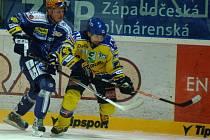 Hokejista Lasselsbergeru Martin Adamský (vlevo) bojuje o puk s ústeckým sokem ve včerejším extraligovém duelu v Plzni. Domácí tým udolal poslední Slovan až v prodloužení 5:4.
