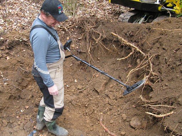 KOVOVÉ DÍLY ZBRANÍ I ČÁSTI VÝSTROJE dokáže najít detektor. Na snímku: místo hromadného hrobu u Málkova prohledává Igor Nachtigall, který u nás zastupuje německý Lidový spolek pro péči o německé válečné hroby Kassel.