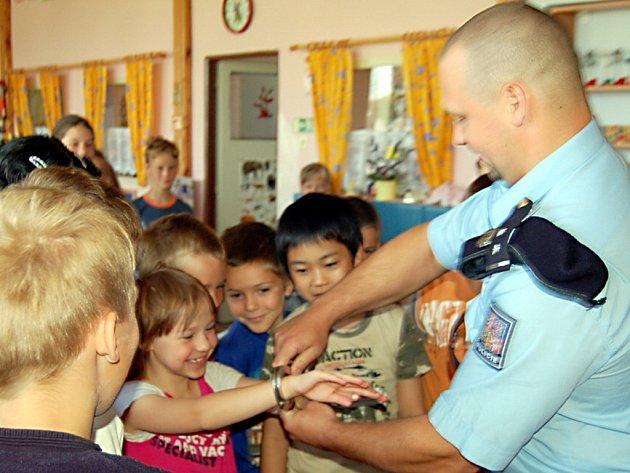 Sotva policista František Krýsl (na snímku) vytáhl pouta, okamžitě se ocitl v obložení dětí. Všechny byly nadšené, když jim náramky sevřely zápěstí.
