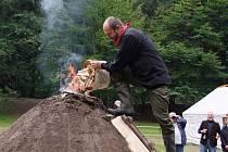 DOPLŇOVÁNÍ KRÁLE není ničím jiným, než dodáním vyhořelého dřeva, které se nasype z horní části milíře. Na snímku tuto práci vykonává Jiří Kadera.
