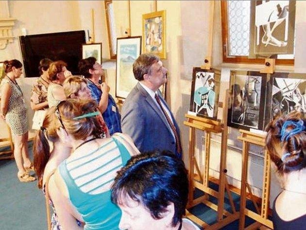 Návštěvníci vernisáže při prohlídce prací Klubu výtvarníků Borska. Výstava v Senátu Parlamentu České republiky potrvá do 17. srpna.