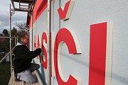 HASIČI - Posledního barevného doladění písma a kontroly se v pondělí odpoledne ujal Jiří Outrata (na snímku) z mariánskolázeňské firmy, která písmena vyřízla ze speciální hmoty, nabarvila a instalovala na boky hasičské zbrojnice.